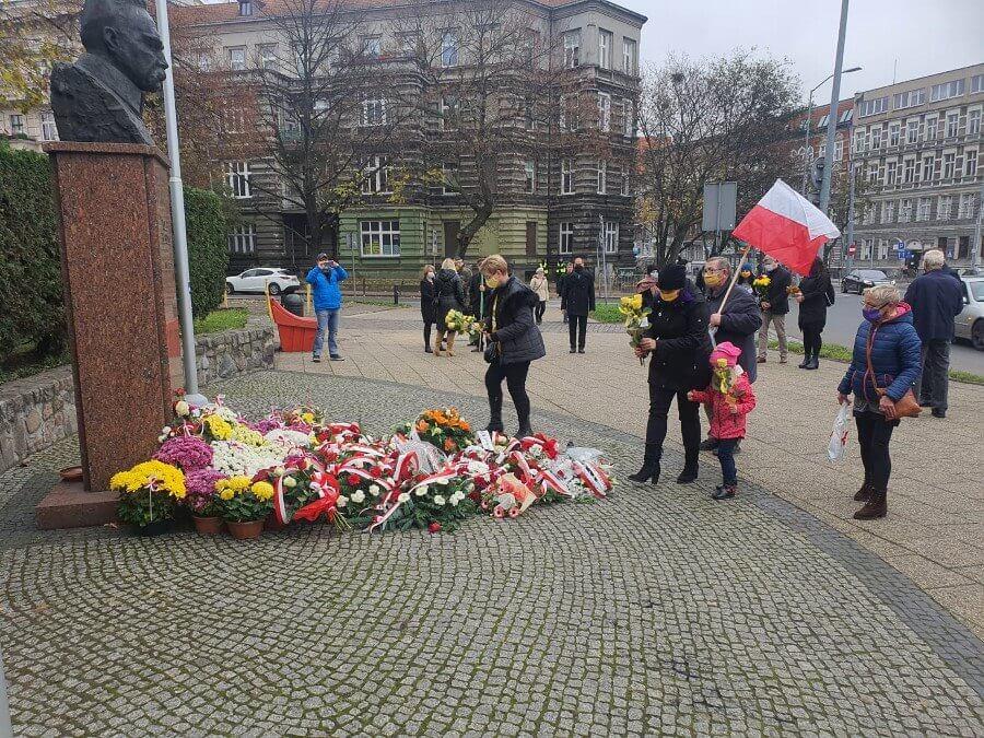Żółte kwiaty pod pomnikiem marszałka.